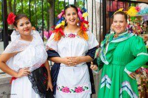 Three adult women wearing white and green traditional dresses with lace and flower embellishments