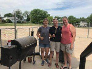 Three women in grey, black, and pink shirts standing next to a black grill while holding metal tongs