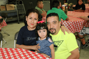 Young Hispanic woman wearing a black bedazzled shirt with her arm around a young Hispanic man in a neon yellow JWV Pork t-shirt holding a small Hispanic girl with a pink bow in her hair wearing a blue and white checkered shirt