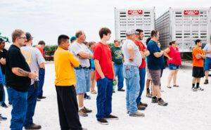 Twenty employees standing outside listening to a person speak with two large silver JWV trailers behind them