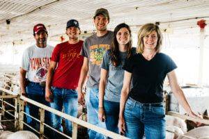 A middle aged married couple standing with their two sons and one daughter smiling in the walkway of a pig barn