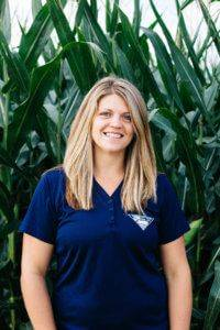 Woman with blonde hair in a navy blue JWV polo smiling in front of a corn field