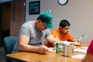Two male JWV employees sitting at a table holding pens and looking at sheets of paper