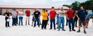 Twenty JWV employees standing outside of their building in a gravel parking lot