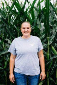 Woman with hair pulled back into a ponytail wearing a gray JWV t-shirt while standing in front of a corn field