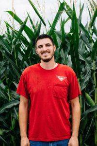 Man with brown hair and beard wearing a red JWV t-shirt with a corn field behind him