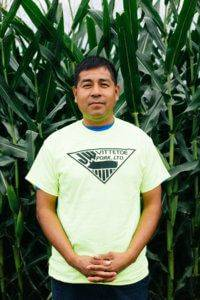 Man with dark hair wearing a neon yellow JWV Pork t-shirt standing in front of a corn field with his hands in front of him