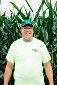 Man wearing a green John Deere hat, glasses, and a neon yellow JWV shirt smiling in front of corn field