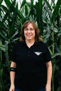 Middle aged woman with glasses standing in front of a corn field wearing a black JWV Pork polo