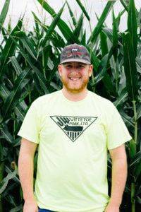 Young adult man with beard and a hat standing in front of a corn field in a neon yellow JWV Pork t-shirt