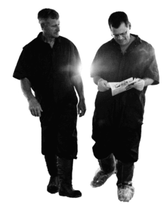 A black and white cutout of two middle aged men wearing overalls and rubber boots walking and looking at sheets of paper