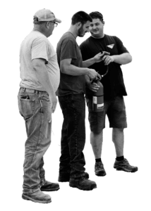 Black and white cutout of three JWV employees standing and the one in the middle is holding a fire extinguisher